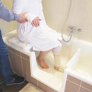 Mozgáskorlátozott személy fürdetése beszerelt fürdőkádajtós kádban